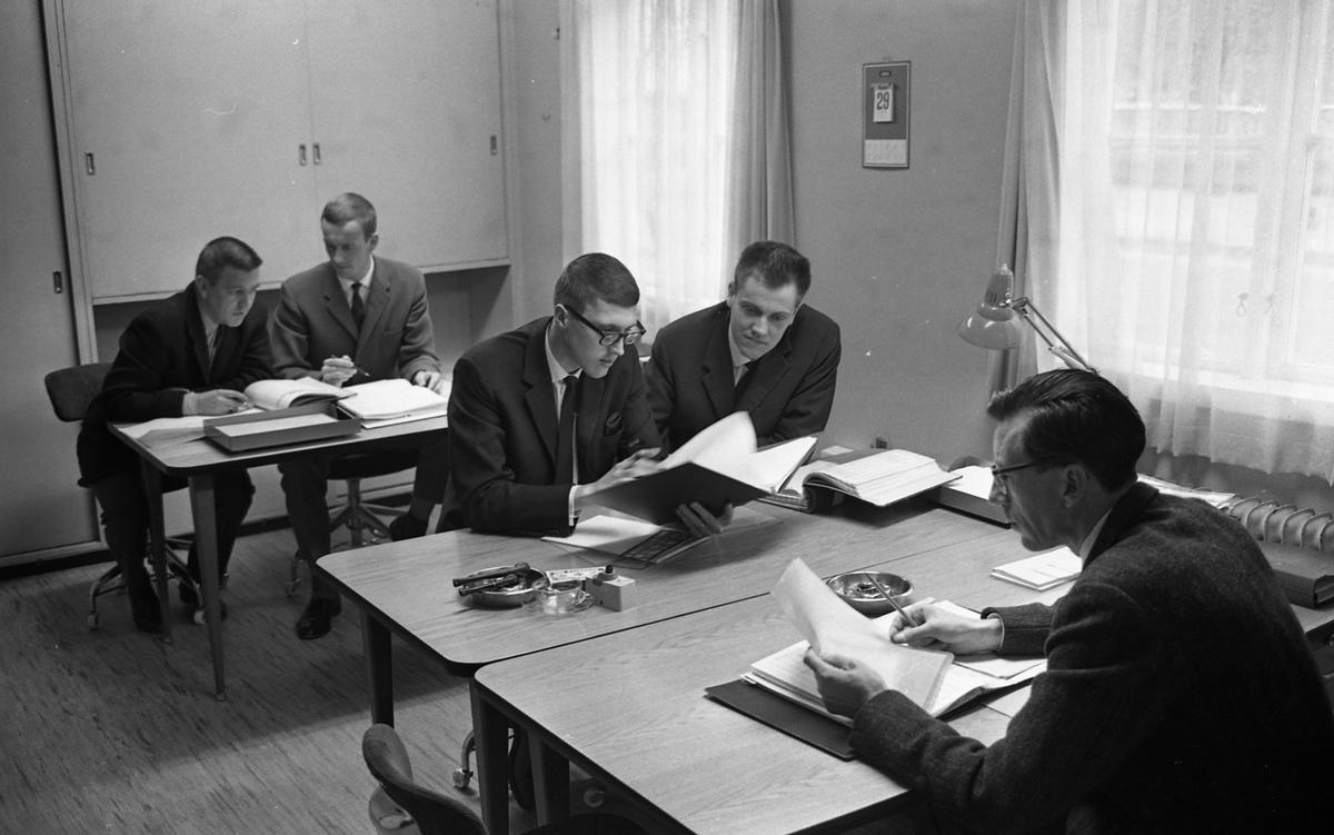 Försvarets Materielverks datorenheten i lokaler i Arboga Margarinfabriks kontor vid Nygatan. Arne Jigelius, till höger, är chef för enheten. Fem män vid arbetsbord. De jobbar med pärmar och papper. På borden finns askkoppar. FMV, CVA, Centrala Verkstaden Arboga