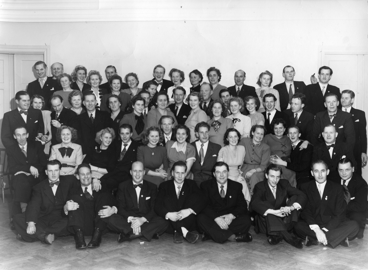 """Gruppbild med kvinnor och män. Människorna är uppklädda. Bilden är tagen inomhus. Någon röker. Harald Larsson (""""Hajan"""") står i bakre ledet, tvåa från vänster. Sammanhang och årtal saknas."""