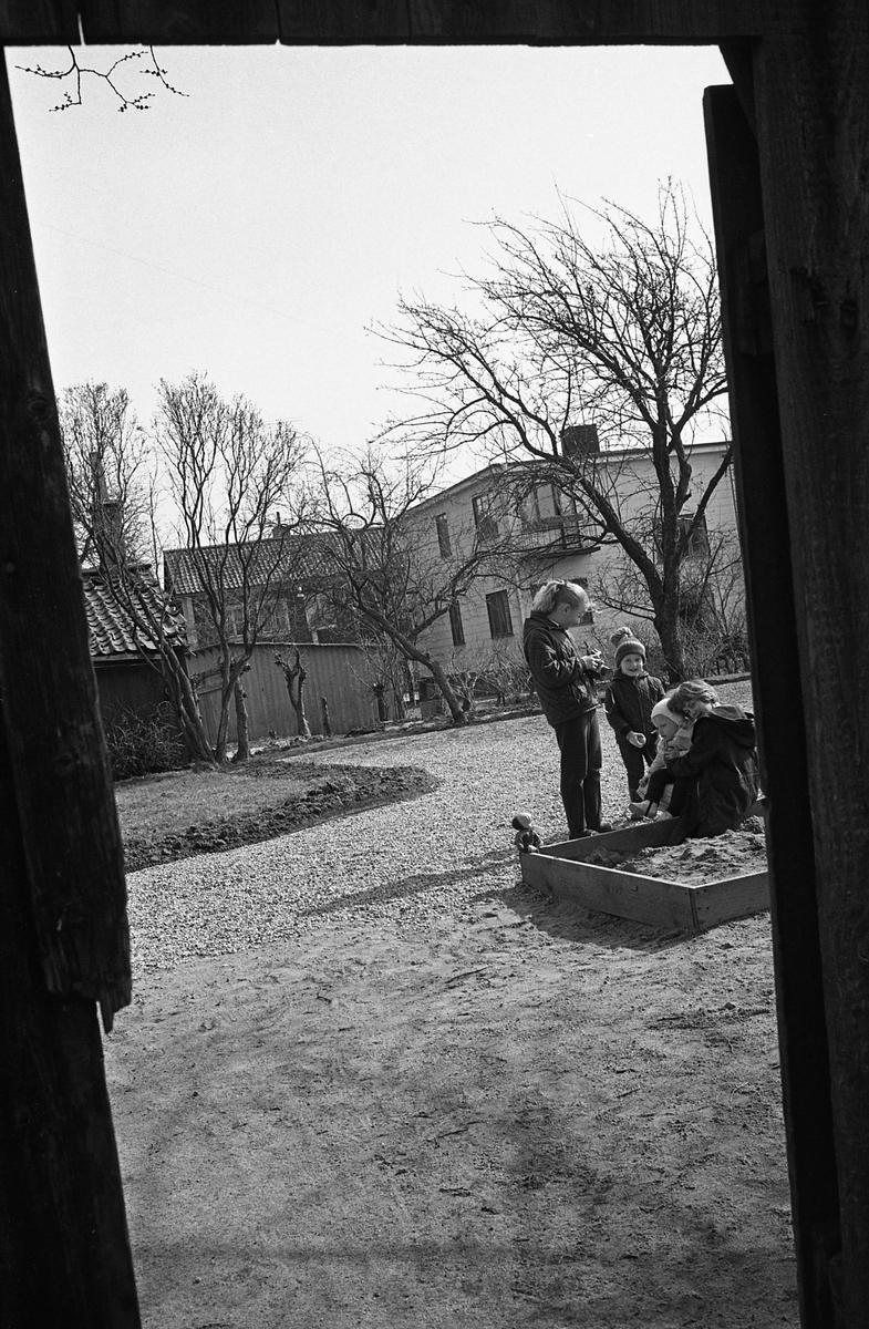 Genom porten ser vi en innegård. Några barn vistas vid sandlådan. Bortom trädgården ses ett nyare tvåvåningshus. Fotografens anteckning: Dokumentation av fastigheter i kvarteren söder och norr om ån. Bilder och beskrivningar finns på Arboga museum.