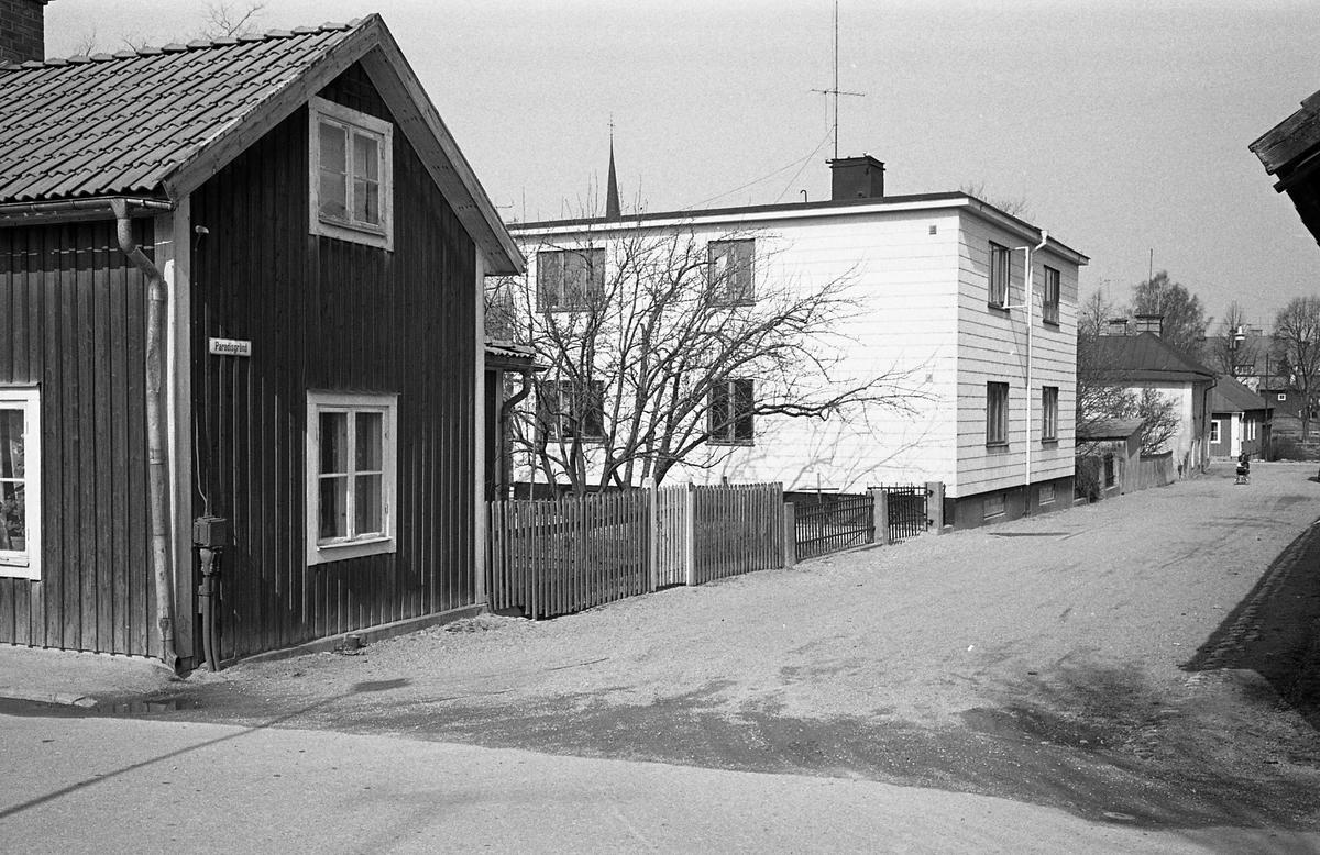 Äldre och nyare bostadshus på Paradisgränd. Trädgård bakom staketet. En person promenerar med barnvagn långt bort i bild. Fotografens anteckning: Dokumentation av fastigheter i kvarteren söder och norr om ån. Bilder och beskrivningar finns på Arboga museum.
