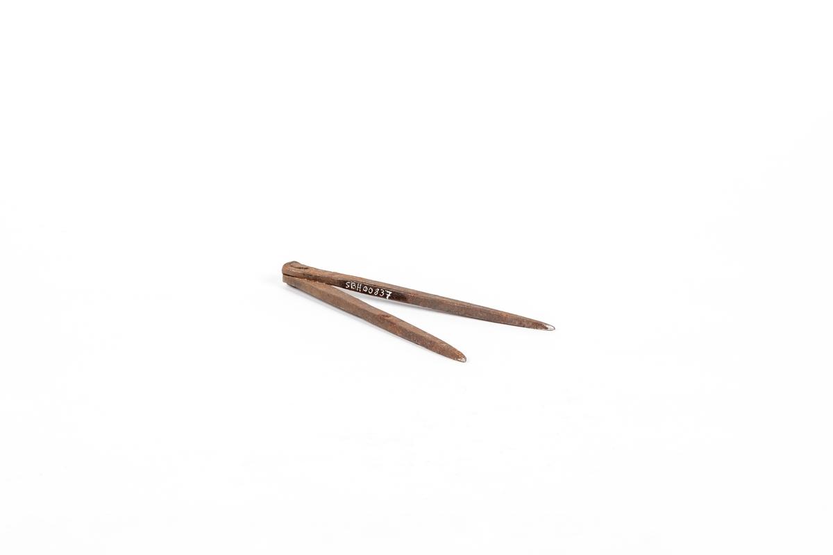 Rett passer bestående av to like ben festet sammen øverst med en nagle. Naglen er banket utover på begge sider.