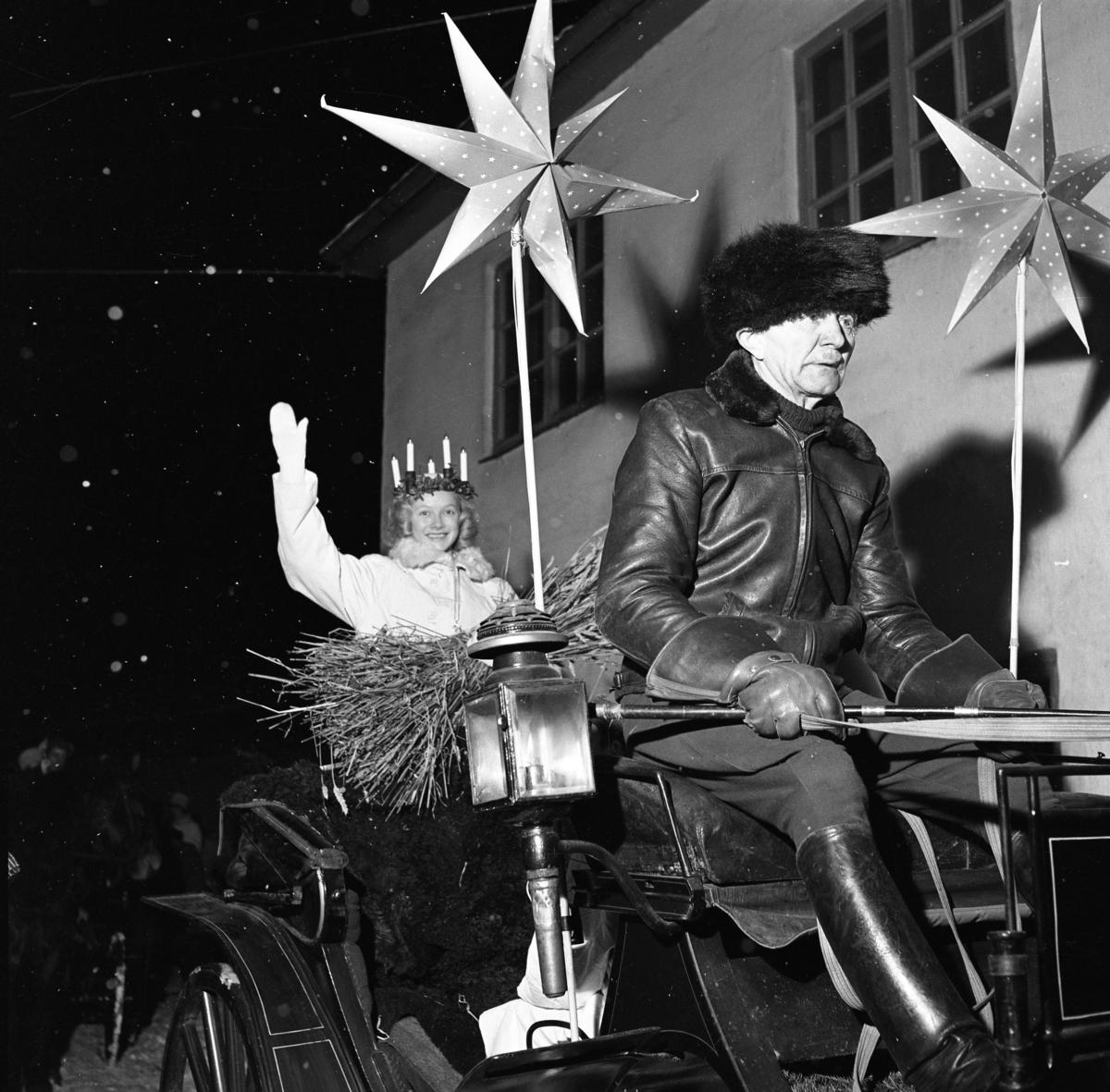 Gustav Jansson, på kuskbocken, kör årets Lucia, Ingrid Zettergren.  Ingrid tyckte att detta var en fantastisk upplevelse men hon frös. Det var -13 grader den kvällen. Hon har batteriljus i håret och en hökärve i knät.  Vagnen är pyntad med julstjärnor och Gustav har en vagnslykta intill sig.