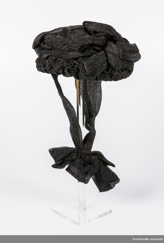 Svart hatt tillverkad av krusig textil i konstfiber, som lagts i olika rosettliknande former. Hakband i samma tyg. Inuti hatten står med guldtext 'Eugenie Rothoff. SUNDSVALL' och på en lös papperslapp liggande i hatten står texten '114 Sorgehatt'. Enligt anteckning 'farmors'.