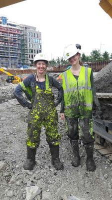 To marinarkeologer poserer etter endt arbeidsdag. Mye leire på klærne