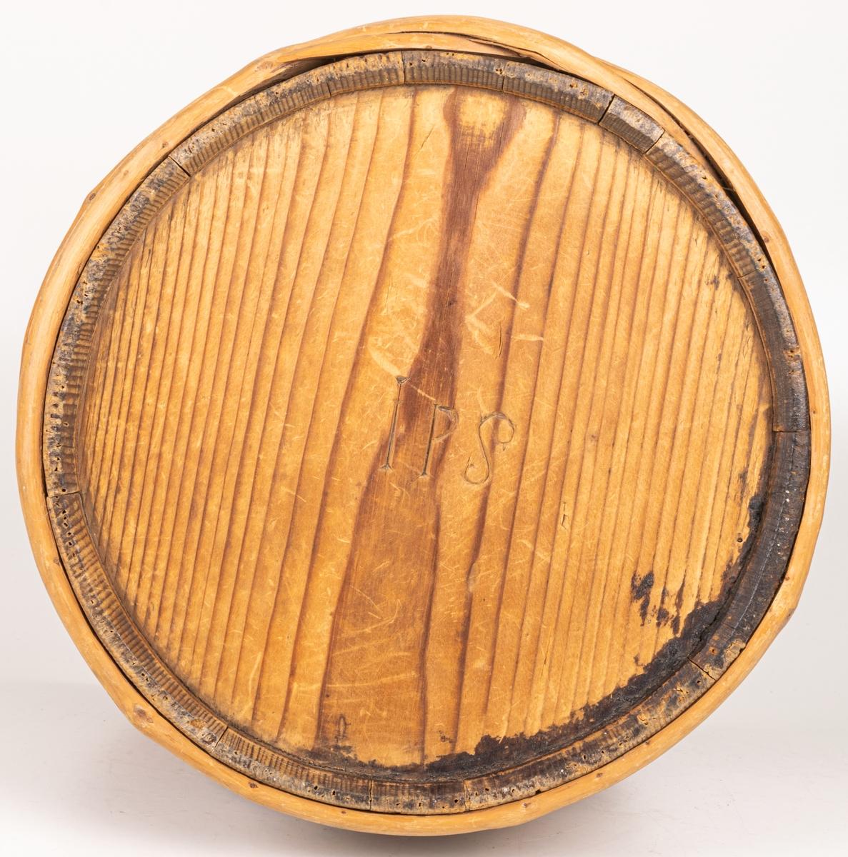 Laggkärl märkt: IPS 1840 5 1/4 Laggad av trä, eventuellt gran. Fyrkantigt hål på sidan. 11 träband.