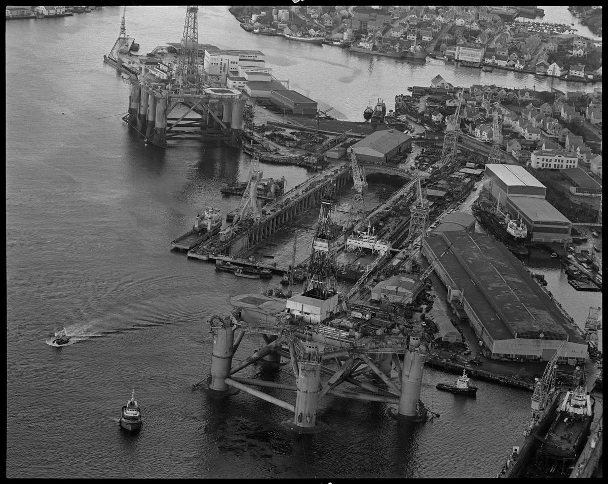 """Flyfoto av vestre del av Risøy med Hasseløy i bakgrunnen. Midt i bildet er tørrdokken til Haugesund Mekaniske Verksted. Riggene """"Fernstar"""" og """"Pentagone"""" og kranlekteren """"Conlift"""" ligger ved verkstedet."""