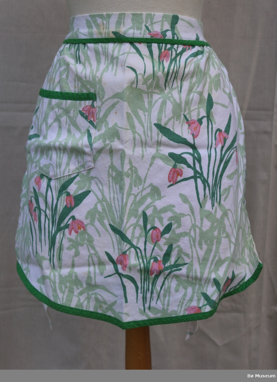 Forkle med lomme. Hovudstoffet har blomar i mønsteret, og i kanten nederst langs falden, langs knytebandet og øverst på lomma er det sydd på ein kant i eit einsfarga grønt soff.