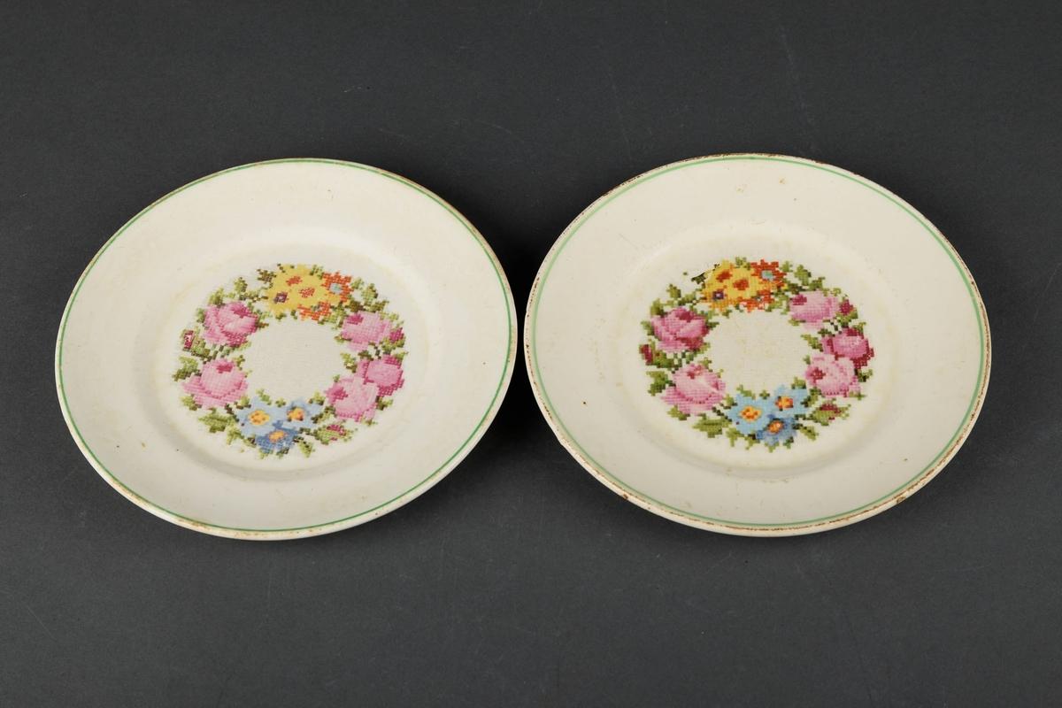 2 hvite tallerkner, dekorert med bilde av en blomsterkrans i midten, og en grønn sirkel langs kanten på overflaten.