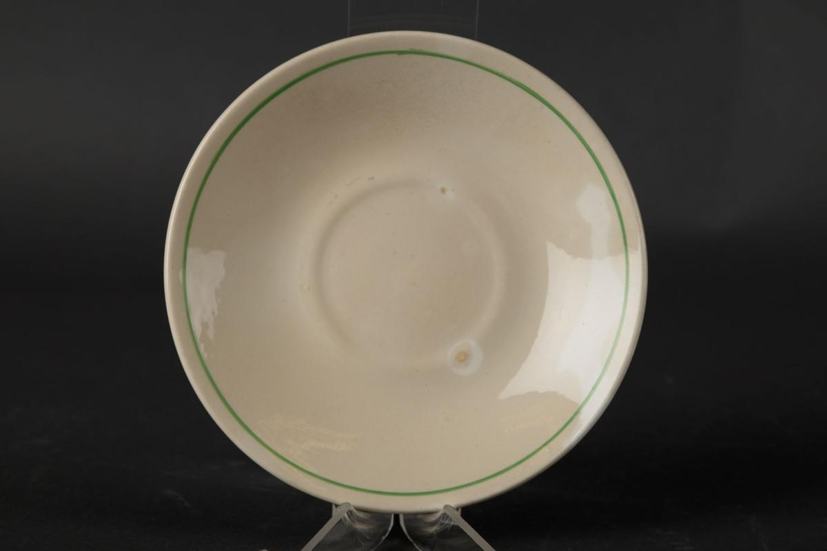 Hvitt tefat med en grønn sirkel langs kanten.