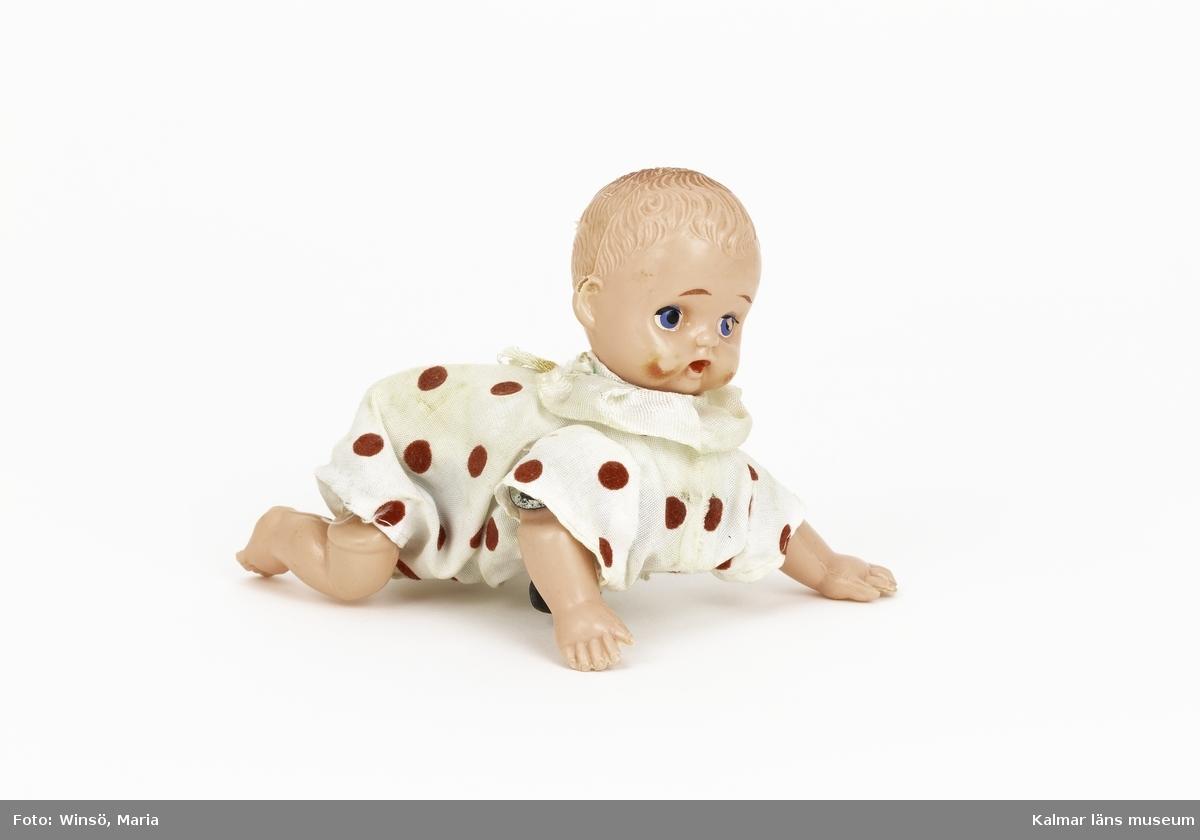 KLM 45519:14 Docka, krypdocka av plast klädd i en vit dräkt med röda prickar och en vit krage. Den har en nyckel på magen och kan vridas upp så att dockan kryper. Ena örat skadat.