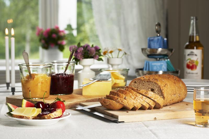 Et pent dekket frokostbord med brød, eplemost, syltetøy og ost. Blomster og levende lys i bakgrunnen (Foto/Photo)