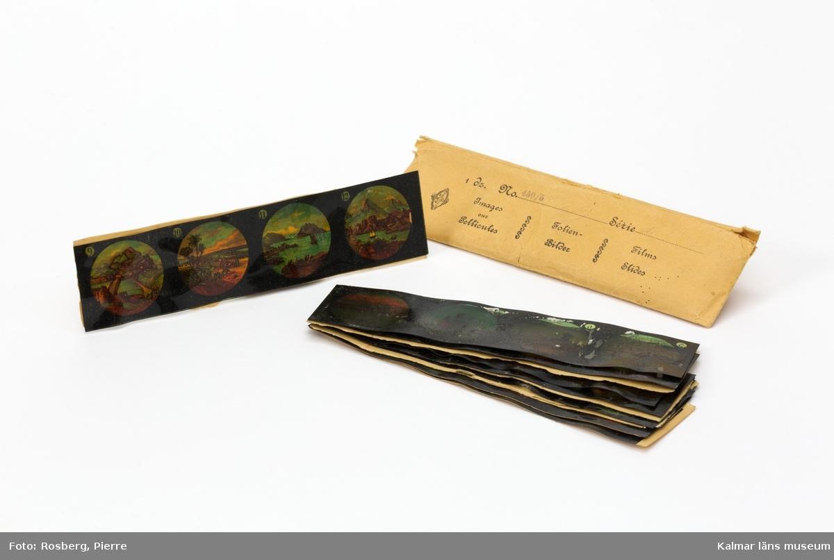 """KLM 45110:10:1-3. Laterna magica med tillbehör, leksak. :1 Laterna magica eller skioptikon, av plåt. Laterna magica av rödmålad plåt med """"skorsten"""" och bildrör i omålad plåt med infästningar för glas, toppen av """"skorstenen"""" i mässingsgul metall. Monterad på en brun träplatta med rund plåt för skål med brännbar vätska. :2 Pappask utan lock, med 14 rektangulära glasplåtar med bilder, längd 11 cm, bredd 3 cm, av glas. Två av glasplåtarna är avslagna. :3 Kuvert, längd 18 cm, bredd 5 cm, med 11 stycken bildserier på film av okänt material. Kuvertet är märkt 1 dz No 450/5 Série A Images our Pellicules FolienBilder FilmsSlides."""