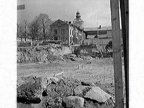 Fastigheten kv Trädgården 6, Varberg. Grundschaktning för Domusbygget är klart. Artikel i samband med bilden publicerad i Varbergs Tidning 1962-05-07. Fotot visar den urschaktade marken och omgivnningarna. Fastigheterna i bakgrunden är Läkaren 9, (Varbergs stadshotell), Rappeska huset (revs 1969?) och en del av Brunnsparken 5.