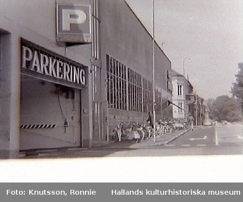 """Domus parkeringshus i Halmstad. Fotot visar infarten till parkeringshuset och längs fasaden står en räcka cyklar parkerade. Bild i samband med miljövårdsutställningarna med bl a, """"Miljön i Halland"""", som visades på museet, 1970-07-03--07-26."""""""