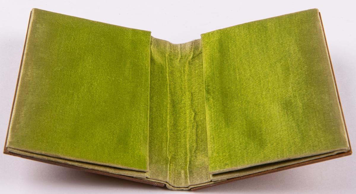 Bok för visitkort med träpärm med skuren uddsnittsdekor. Inuti klädd med grönt siden.