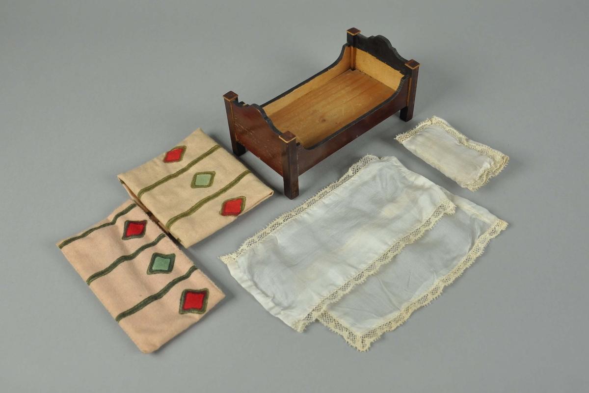 Lekemøbler av brunfernisert treverk med gulldekor. Består av toalettkommode, toalettbord, vaskeservant, seng, sengeklær - madrass, laken, pute, overlaken, dyne, skittentøypose, nattpotte, og sokkelbord. Vaskeservanten har bord av marmor.