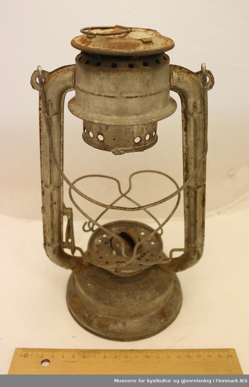 En parafinlampe med vekebrenner. Parafinbeholderen er festet i rammen til glasset, som gjør lampen til én sammenhengende konstruksjon. Glasset til lampen mangler. Brenneren og festet til lampeskjermen kan løsnes.