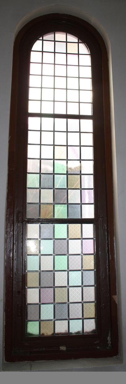 Dekorvinduet her vært hengslet fast i et fastkarmvinduet som beskyttet det for vind og vær fra yttersida. Vinduet er høyt og smalt og består av et stålramme med tre felt. Det øverste har et halvrund avslutning oppe. I hvert felt er eller har vært innsatt med bly, fem ganger syv, rektangulære, fargede glassruter. Fargevariasjonen rekker fra gul- over grønn-, helt til lillatoner. Det må har vært et pent fargespill på innsiden av kapellet når sola skinte inn.