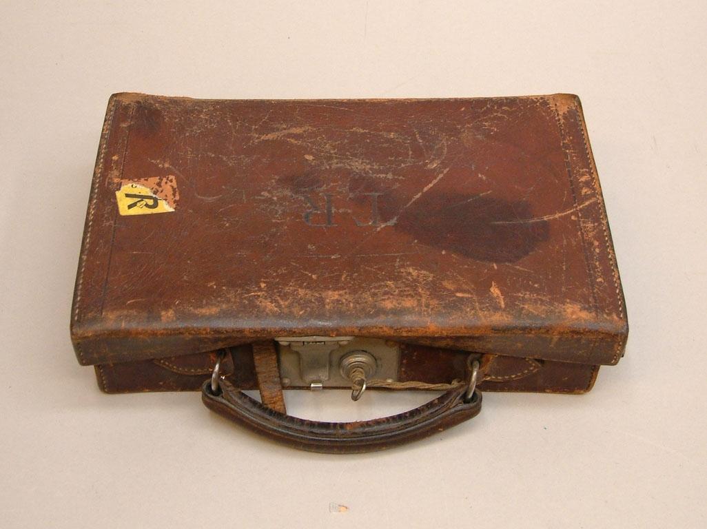 """Liten väska i brunt läder med TR märkning stansat på locket. Handtag av dubbelsytt läder, ett lås med nyckel ovanpå samt en rem att fästa locket med.  Gult klistermärke av nyare modell på framsidan med TR-pojken på. Det har stått """"ÖL"""" på det, men det är bortrivet."""