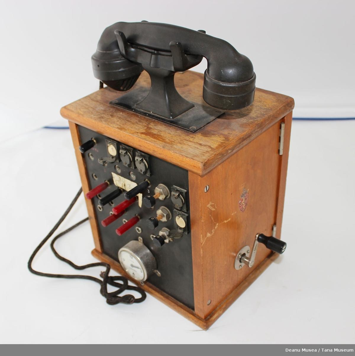 Liten manuell telefonsentral med sveiv. Huset er lagd av tre.