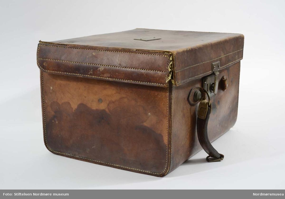 Koffert av skinn med messinglås med enkel lukkemekanisme i front. Innsiden er foret med grønn silke og lokket har to lærreimer som stopper den i å falle helt tilbake