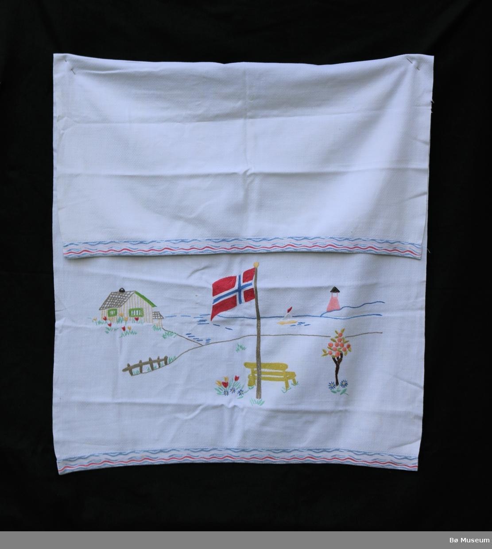Pyntehandkle (a) og løper (b) med nær identiske motiv (brodert). Motivet består av ei hytte ved sjøen, flaggstang med norsk flagg, ein benk og blomar ved flaggstanga. Seglbåt og fyrhus i horisonten. Band med stripete mønster (trykk) langs kantane på både pyntehandkle og løper.