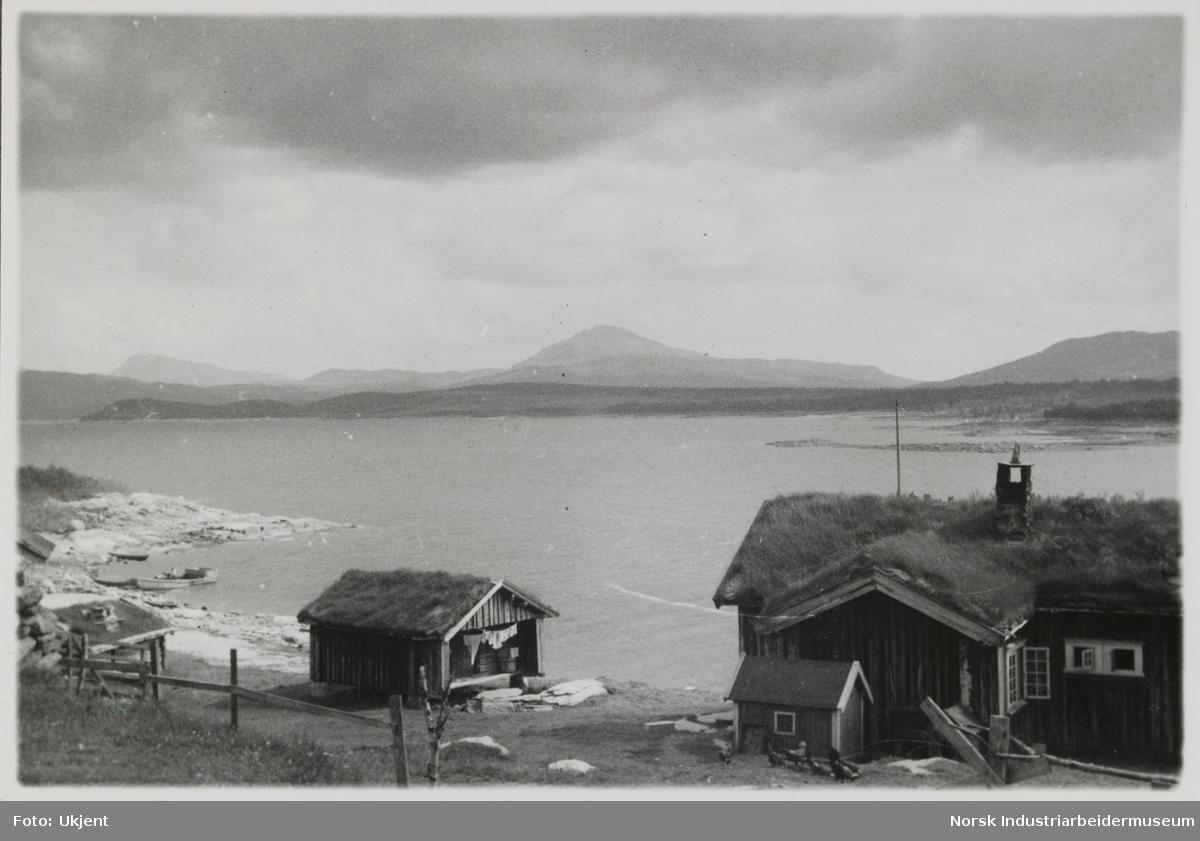 Husbygninger står ved vannkanten, innsjøen Møsvatn