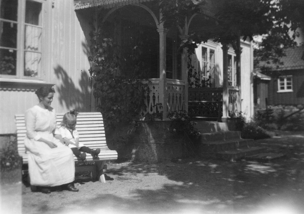 Kvinne og barn på en hagebenk foran et større våningshus