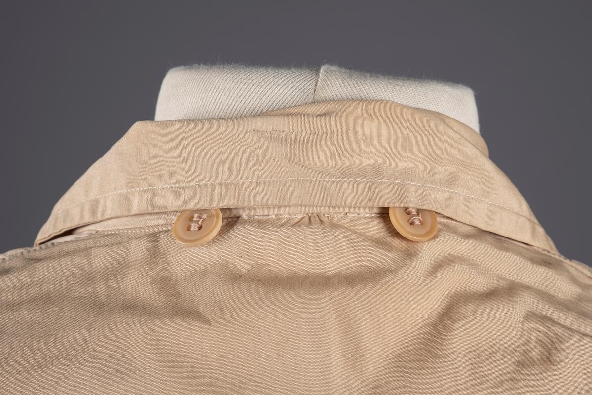 Anorakk med strikk i livet. Den kneppes i front og har to forlommer. Det mangler en knapp og en av knappene er erstattet med en annen knapp. Det er smale mansjetter på ermene med knepping. På innsiden av kragen er det en hempe for oppheng.