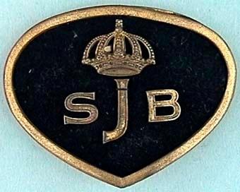 Sköldformat mössmärke med oval ovansida och spetsig avslutning nedtill. Märket är av plåt klädd med svart kläde. Det har en smal gyllene kant och bokstäverna SJB krönt av kunglig krona på mitten.