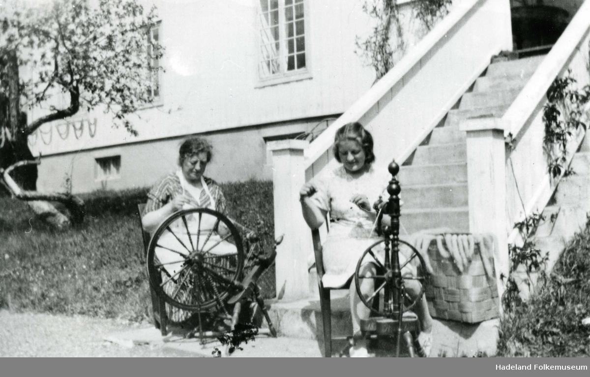 Prestefrue Margrete Tronsdatter Gamkinn og datteren Tora Gamkinn spinner på hver sin rokk utenfor Jevnaker prestegård.