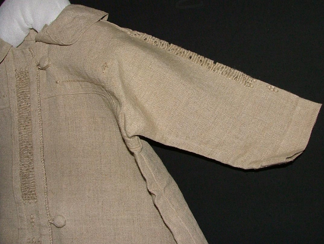 Av oblekt kraftig linnelärft, utsvängd modell med sidsömmar samt långa ärmar skurna i ett med besparing, svängd krage bredare bak än fram, i framkanten påsydd knäppslå dekorerad med broderi i enkel utdragssöm, samt i kanten en flätad snodd som även bildar tre tränsar och knäpps med tre överklädda kupade knappar, samma broderi längs med ärmen, besparingen markerad med en rad kedjesöm.