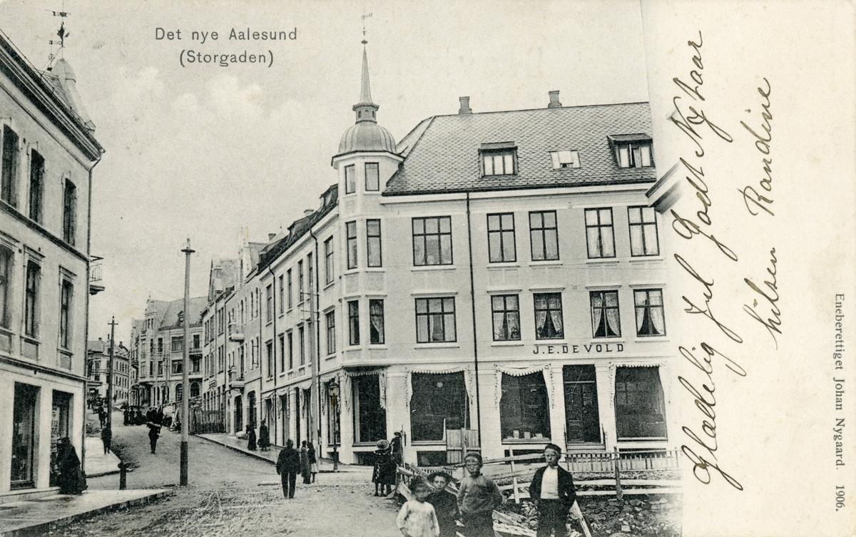 Motiv av gatemiljøet i Storgata, Ålesund. J. E. Devolds butikkbygning til høyre i bildet.