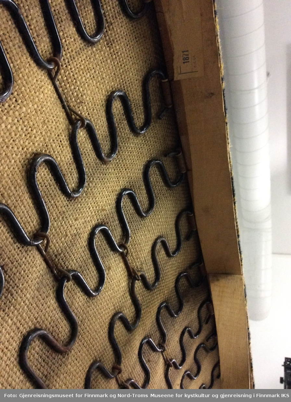 Sofaen er en treseter med stripet trekk på sitteflaten og grønt trekk på ryggstøtta. Benene er smale og skråstilte. Bakbenene er også støtte til armlenene. Sitteflaten består av ei ramme med to tverrforbindelser. I ramma er det festet serpentinfjærer som igjen er festet til hverandre. På innsida av ramma på fremsiden, er det limt fast en etikett med produsentopplysninger. På fjærene ligger striestoff deretter kommer polstringsmaterialet og trekkstoffet øverst.Trekkstoffet er stiftet fast på undersiden av ramma. Frambenene sitter litt løst.
