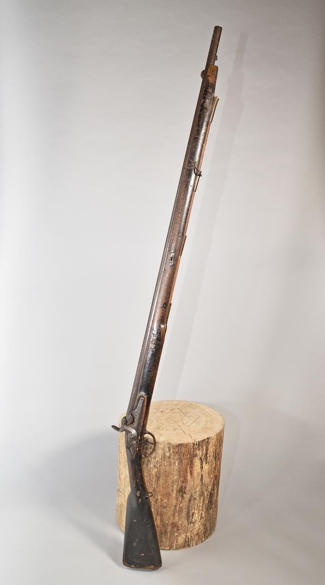 """Mynningsladdad bössa med slaglås. Kolv och stock av svartmålat trä, beslag och laddstakshylsor (4 st) av mässing, laddstake av trä (avbruten i toppen), avlångt korn av mässing. Slätborrad pipa. Tjockt låsbleck med varhake (och """"stopptapp""""). Rutat tumgrepp på hanen. På låsblecket stämplat """"K"""", """"TF"""" samt """"C 663""""; """"K"""" även på pipan och snäckan, """"663"""" även på stocken. På sidbeslaget """"I C 101 K O IHH"""". Inskuret på kolvens undersida """"FH""""."""