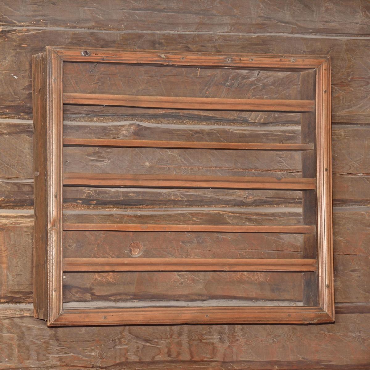 Hylla av omålat barrträ, rektangulär form, väggfast. Ram av brädlappar, randhyvlade kantlister och slåar, två hyllplan, hopsinkad.