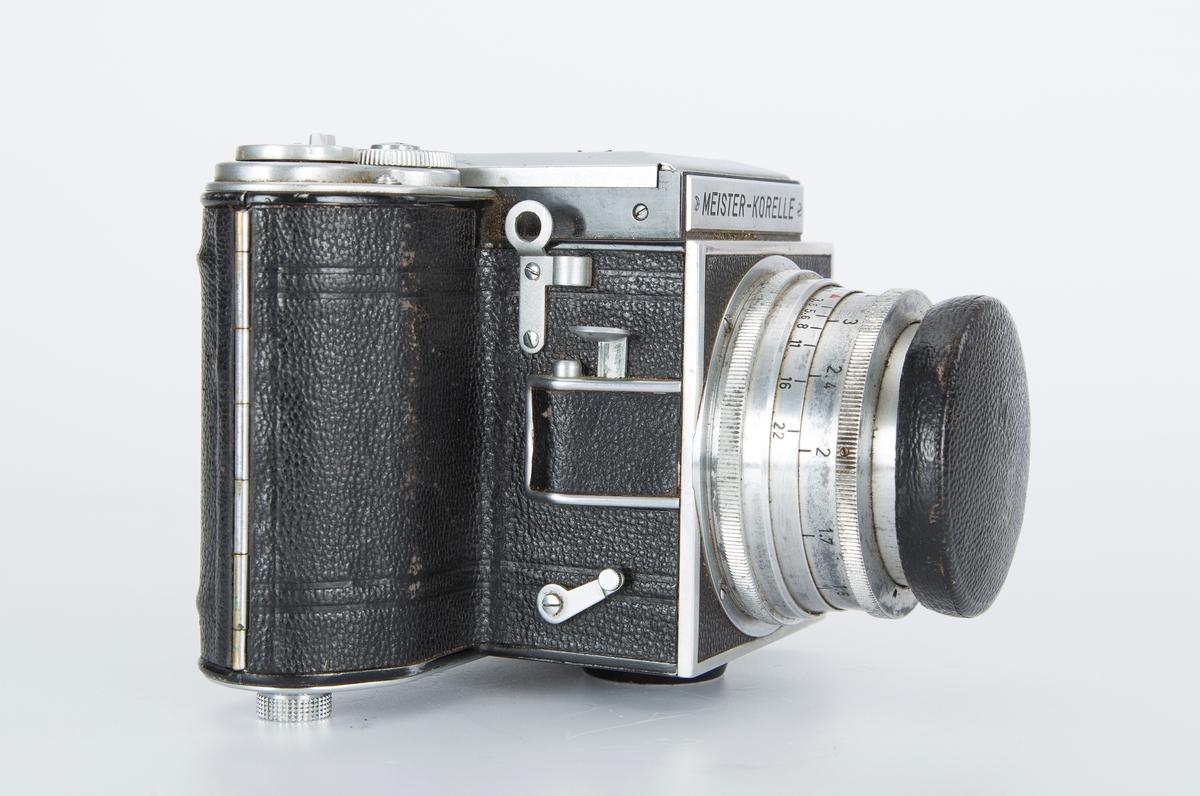 Kamera med linse. Metallfirkant rundt søker. Brun kameraveske