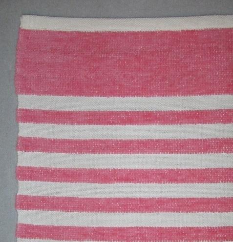 """Tvärrandig handduk, tre stycken, vävd i tuskaft med blekt tvåtrådigt bomullsgarn i varpen och färgat velourgarn och blekt tvåtrådigt bomullsgarn i inslaget. Innanför den smala maskinfållade fållen i vardera kortsidan har handduken en 50 mm bred velourrand och sedan centimeterbreda ränder, varannan i blekt bomull och varannan i färgad velour. En handduk har grå ränder, en rosa och en ljust blågrå. Ett smalt vitt band är fastsytt  som hank mitt på ena kortsidan.På den grårandiga handduken är en vit fyrkantig klisterlapp fastsatt med en häftklammer. Texten lyder: """"Grå-vit handduk chenille Skarab. Hemslöjd"""". I andra kortsidan är den märkt med R3:1 på ett fastsytt vitt bomullsband. Den rosa handduken har en vit klisterlapp med maskinskriven text: """"Tvärs"""" klistrad på ena sidan och är märkt med R3:2. Den ljust gråblå är märkt R3:3.Handduken  med modellnamnet Tvärs är formgiven av Ann-Mari Nilsson och tillverkad av Länshemslöjden Skaraborg. Den finns med  på sidan 12-13 i vävboken Inredningsvävar av Ann-Mari Nilsson i samarbete med Länshemslöjden Skaraborg från 1987, ICA Bokförlag. Se även inv.nr. 1,2,4-40."""