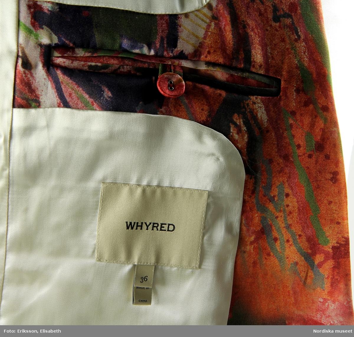 """Blazer för kvinna, """"Woman's Blazer"""", maskinsydd av mönstrat, tryckt sidentyg i rak modell med smala slag. Två diagonalt placerade klädda knappar framtill, fickor infällda i sidosömmarmarna. Rakt skuren nedre kant, rundad i mötet framtill, sprund nedtill i ryggen. Det tryckta sidentyget i röda nyanser har även inslag av brunt, grönt, gult och vitt. Innerfoder av  crèmefärgat sidentyg, smal beige etikett av läder med text: Whyred, fastsydd på insidan vid nacken (lossnat på ena sidan). I brösthöjd en innerficka på vardera sida, knäppt med klädd knapp. Under vänstra fickan en beige sidenetikett med text: WHYRED, samt fastsydda i etikettens nedre söm, vita sidenband med tryckt text: 36. Made in China. Lisa Eide 2015-03-26, Helena Lindroth 2019-01-21"""