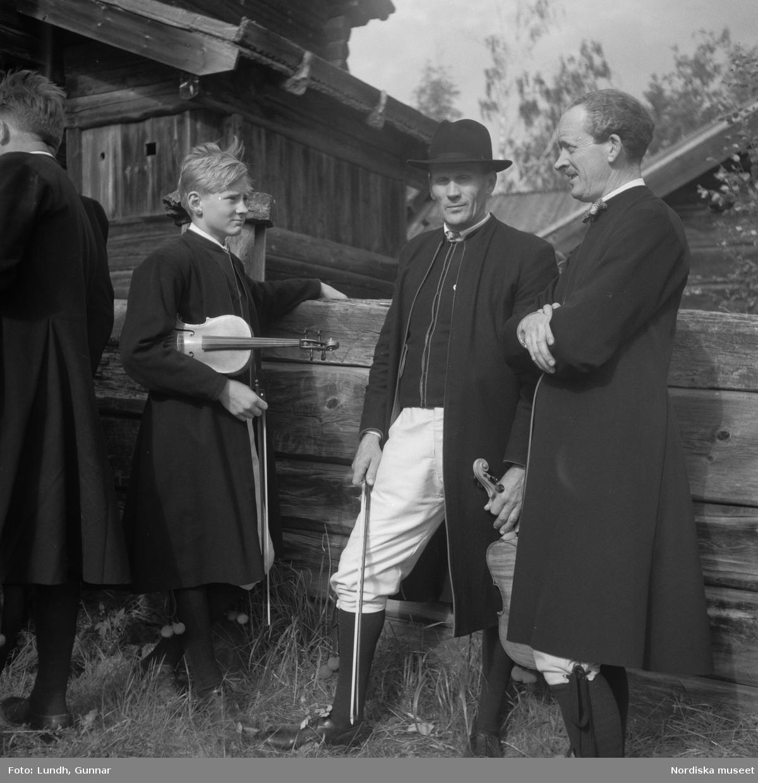 Motiv: (ingen anteckning) ; Porträtt av en man - ett barn och en kvinna i folkdräkt, två kvinnor i studentmössor, män klädda i folkdräkt spelar fiol.