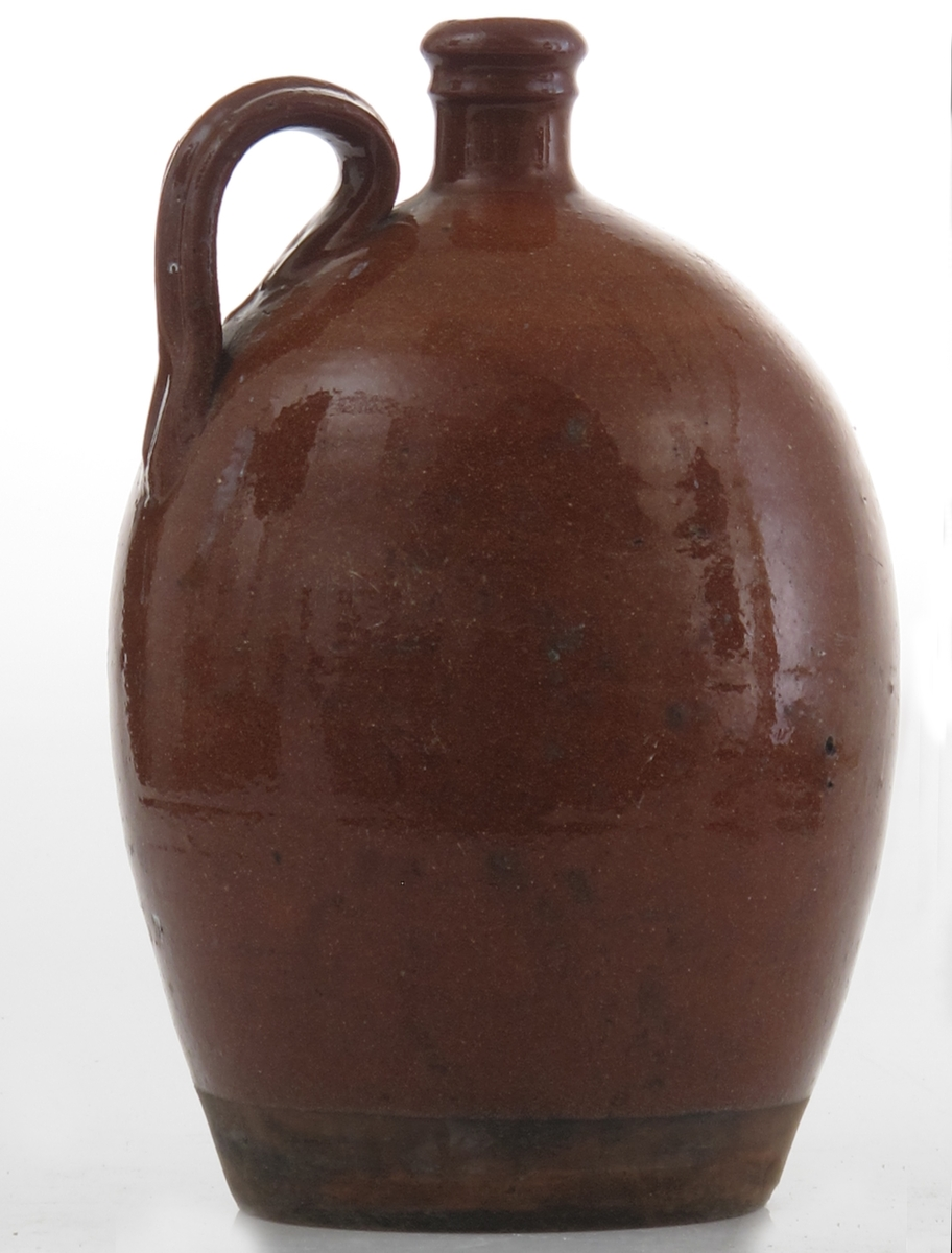 Krukke. Leirtøy, blyglasur. brun, blank glassur. Ørehank. Tilstand nov. 1960: God..