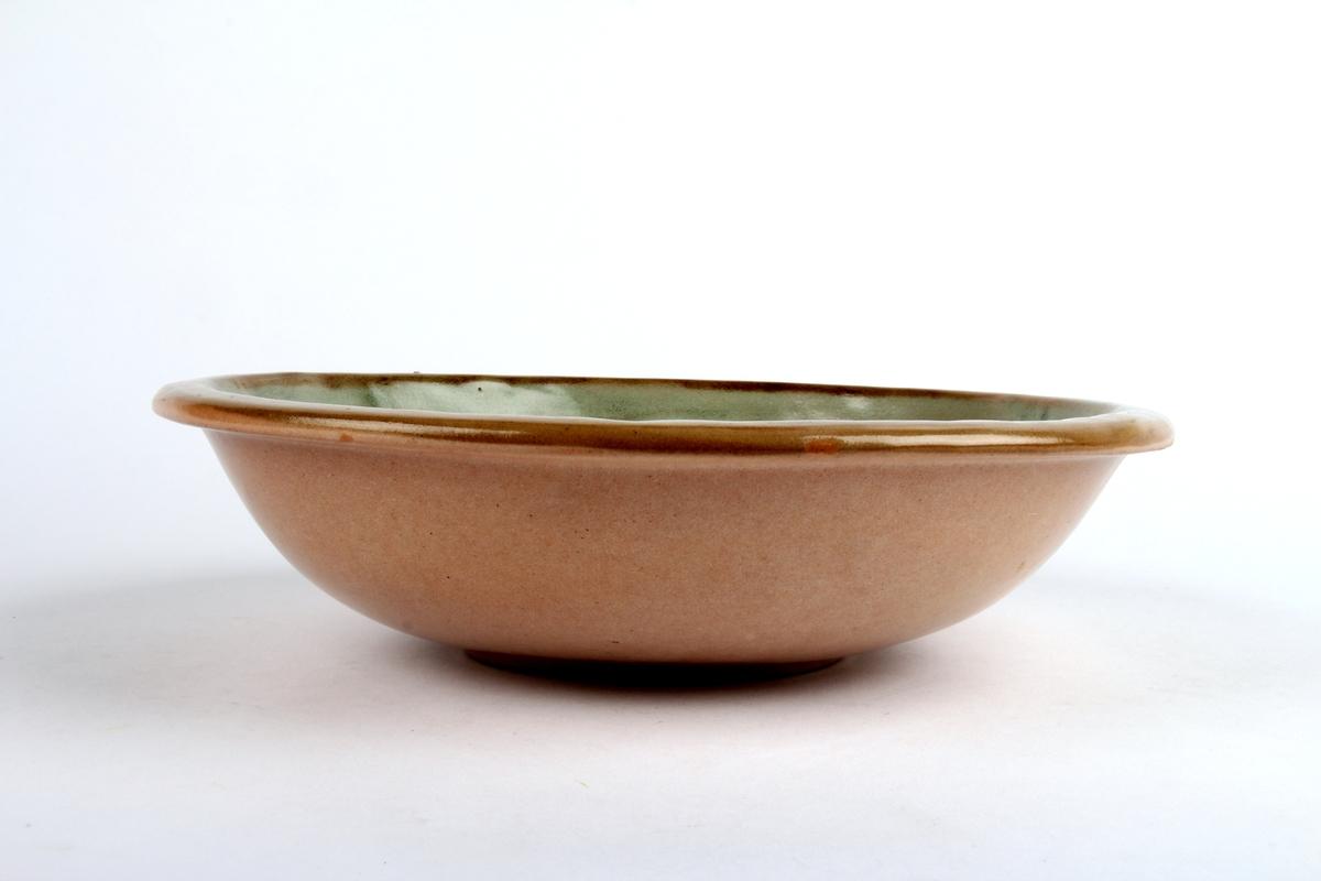 Glasert keramikkskål med riller i bunn og grønn rekor.