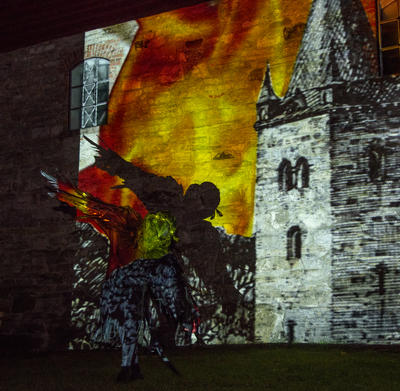 En svart fugl flyr foran en videoprojeksjon av middelalderkatedralen som brenner. (Foto/Photo)