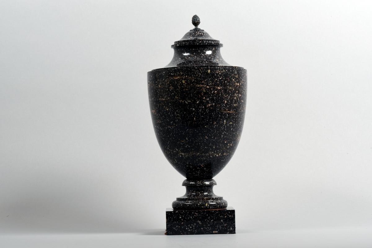 En av två urnor med lock av porfyr från Älvdalen. Kvadratisk fot. Locket har en knopp i form av en bladkransad pinjekotte av silver. Urnan är i tre isärtagbara delar.