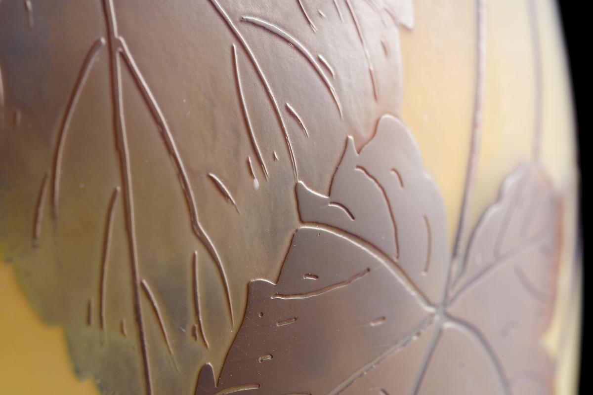 Halvopak, gulvit vas med etsat överfång i blå nyanser. Växtmotiv med blad och bär på kvist.