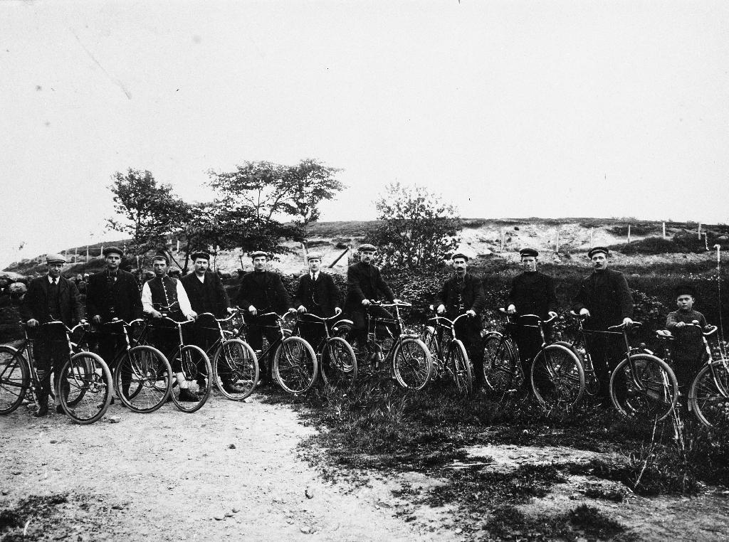 11 menn med syklar på vegkanten.