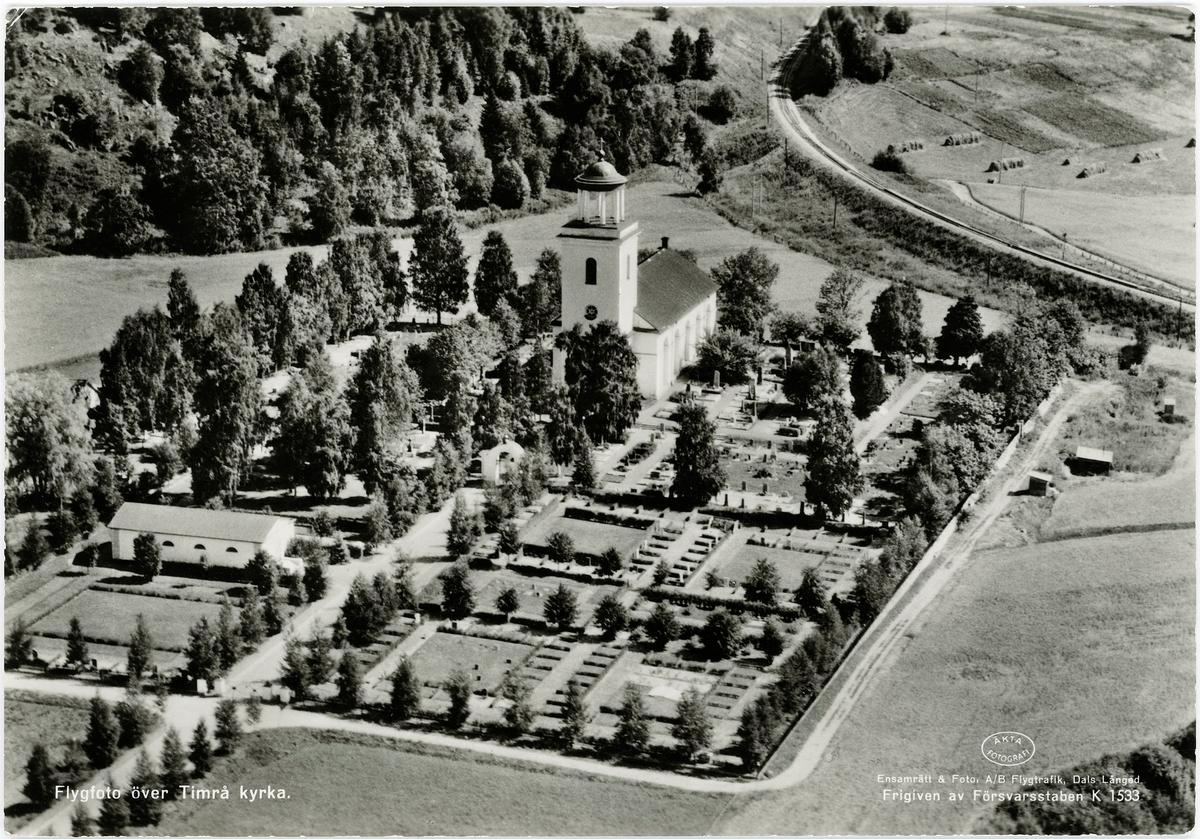 Flygfoto över Timrå kyrka med kyrkogård. Vykort.