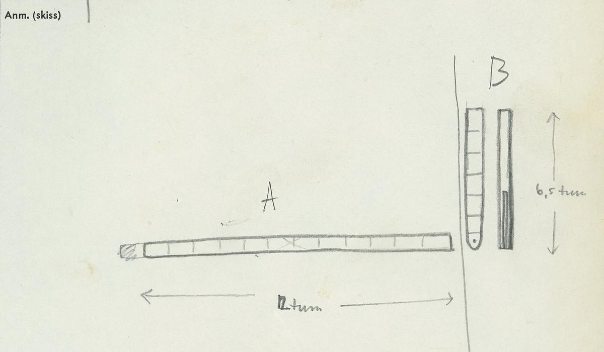 En tumstock av trä. Tumstocken är försedd med elva inristade skåror som markerar tolv tum. På den mittersta skåran finns ett inristat kryss. Ytterligare ett kryss, dock något mindre, har ristats in vid skåran närmast mittskåran. Tumstocken är i gott skick.