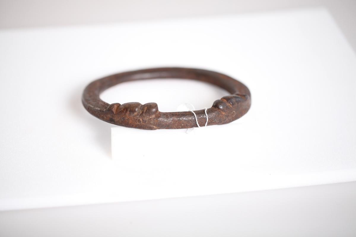 Oval, glatt smidd ring. To dyrehoder (ormehoder) vender mot hverandre og i munnen holder de ringen. Innslåtte ringer rundt på dørringen.