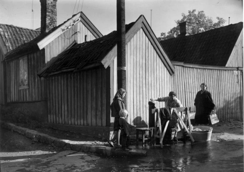 Klesvask ute ved vannposten foran Johannes gate 12/14 i 1959.